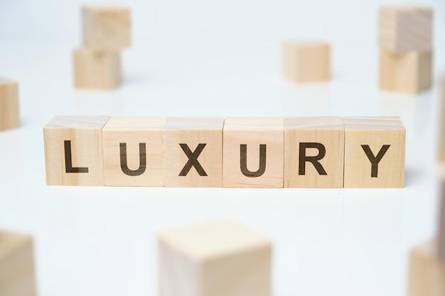 Modern zakelijk modewoord - luxe. word op houten blokken op een witte ruimte.