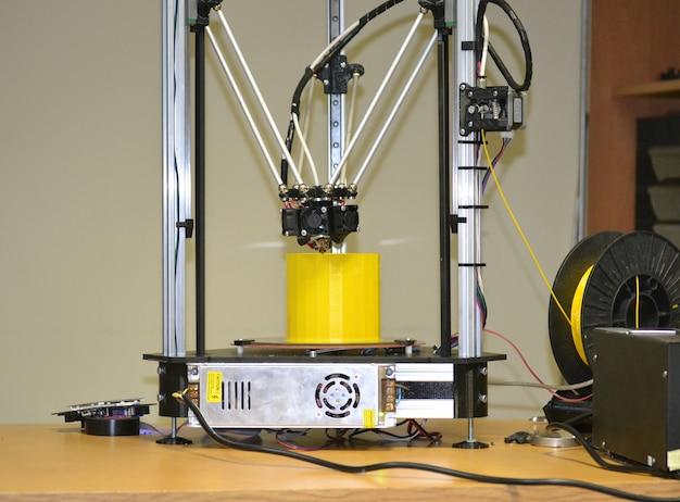 Moderne 3d-printer afdrukken figuur close-up. automatische driedimensionale 3d-printer voert plastic gele kleurenmodellering uit in het laboratorium. progressieve moderne additieventechnologie
