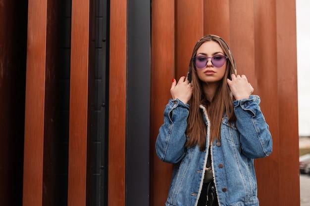 Moderne aantrekkelijke jonge vrouw in stijlvol blauw denim jasje in militaire hoodie met modieuze paarse bril poseren in de buurt van een metalen vintage muur buiten. trendy hipster meisje in de stad. street style.