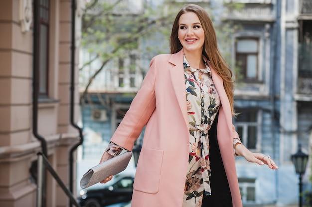 Moderne aantrekkelijke stijlvolle lachende vrouw stad straat in roze jas lopen