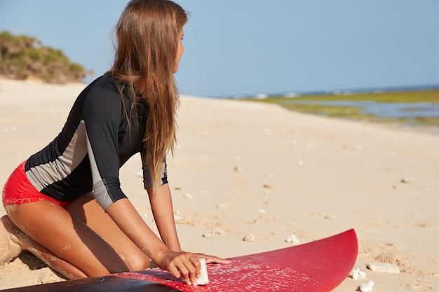 Moderne actieve sport, zomervakantie concept. horizontale weergave van actieve surfer gekleed in wetsuit