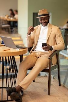 Moderne afro-amerikaanse man aan het werk in een caffe