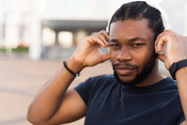 Moderne afro-amerikaanse man zijn koptelefoon zetten