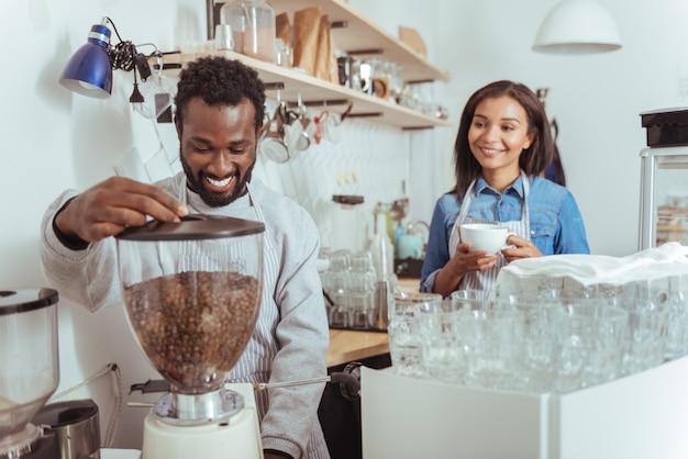 Moderne apparatuur. charmante jonge mannelijke barista die een koffiemachine gebruikt om koffie voor zichzelf te zetten terwijl zijn vrouwelijke collega al een kopje koffie vasthoudt