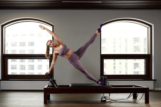 Moderne apparatuur studio reformer voor pilates in de sportschool, concept van herstel en revalidatie, de instructeur voert oefeningen uit op de studio reformer om het bewegingsapparaat te corrigeren.