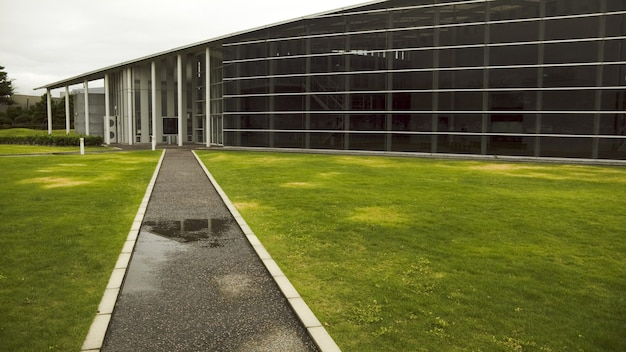 Moderne architectuursamenstelling, glazen wand en rechte weg naar de ingang van de hal Premium Foto