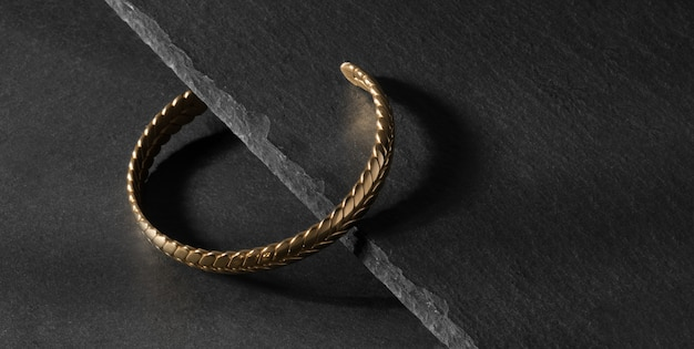 Moderne armband in vlechtvorm gelegd op zwarte stenen plaatrand met kopieerruimte