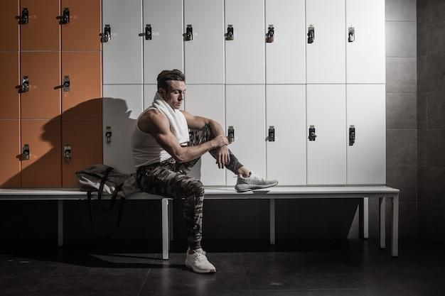 Moderne atleet die op bank rust