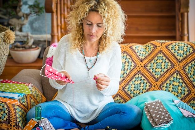 Moderne baan thuis coronavirus covid-19 - vrouwelijke mensen bereiden medische maskerbescherming voor quarantainebeperkingen voor lockdown - kleurrijke modieuze trendy maskers en creatieve vrijetijdsbesteding binnenshuis