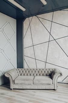 Moderne bank in grijze stijlvolle kamer. lege moderne bank van grijze kleur. love seat moderne bank in studio in grijstinten.