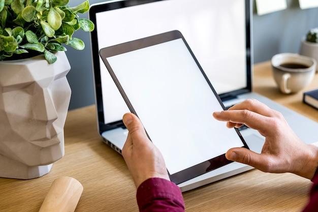 Moderne bedrijfssamenstelling op het thuiskantoor met freelancer, tabletscherm, plant, notities, mobiele telefoon en kantoorbenodigdheden in een stijlvol concept van huisdecor.