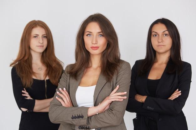 Moderne bedrijfsvrouwen in kostuum met hun gekruiste wapens status op grijze achtergrond.
