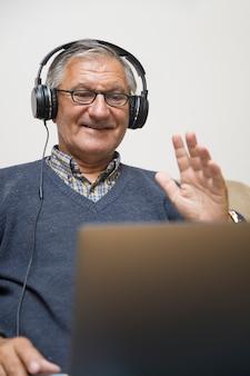 Moderne bejaarde die thuis met oortelefoons situeert en online videogesprek heeft