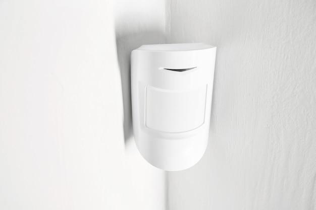 Moderne bewegingssensor op de muur binnenshuis