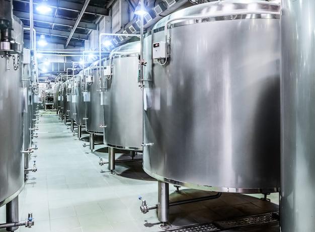 Moderne bierfabriek. rijen stalen tanks voor bierfermentatie en rijping. blauw vlek lichteffect