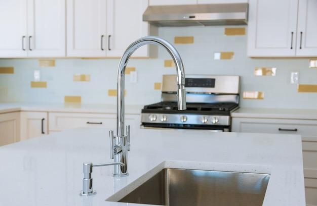 Moderne binnenlandse kasten met nieuwe apparaten en gootsteen in keuken