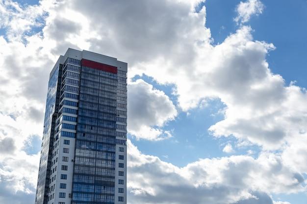 Moderne blauwe en witte stenen condo-toren op blauwe lucht op de achtergrond