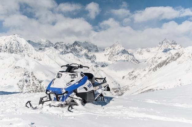 Moderne blauwe sneeuwscooter op de achtergrond van sneeuwbergen