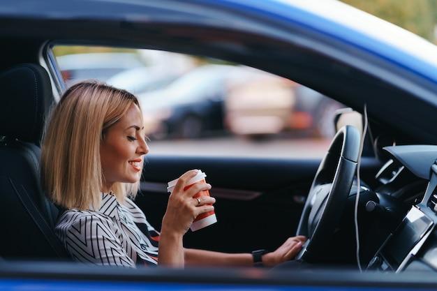 Moderne blonde vrouw met een kopje koffie tijdens het rijden in de stad
