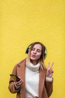 Moderne blondevrouw die aan muziek op hoofdtelefoons luisteren