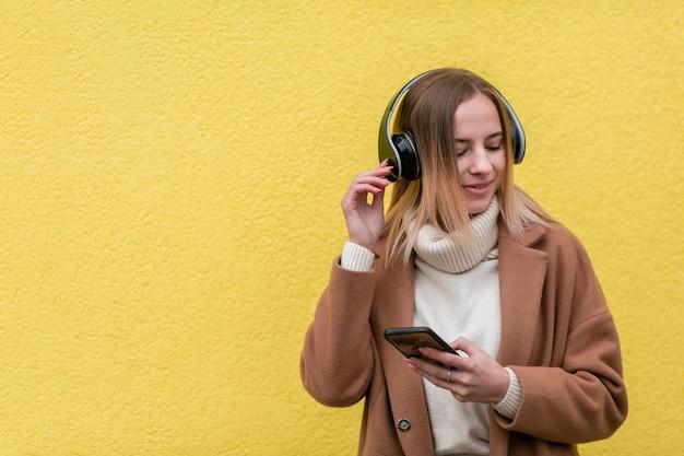 Moderne blondevrouw die aan muziek op hoofdtelefoons met exemplaarruimte luisteren
