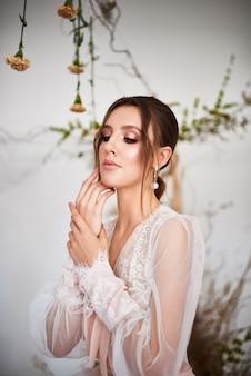 Moderne bruid die in gevoelige lingerie op huwelijksochtend draagt. zeer mooie jonge vrouw op een witte achtergrond met natuurlijke bloemen