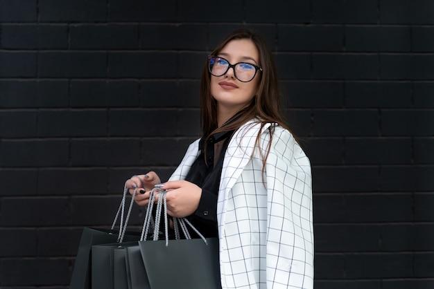 Moderne brunette vrouw in glazen houdt papieren boodschappentassen tegen zwarte bakstenen muur achtergrond.