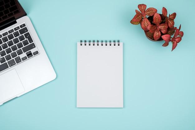 Moderne bureau tafel met computer, lege notebook pagina en rode plant