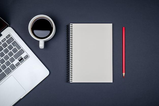 Moderne bureautafel met laptop en lege notitieboekjepagina