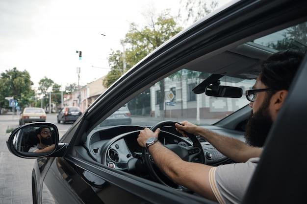 Moderne casual bebaarde man autorijden