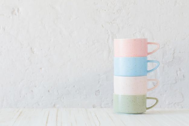 Moderne ceramische koppen op witte muur als achtergrond