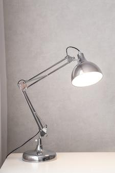 Moderne chromen bureaulamp ingeschakeld.