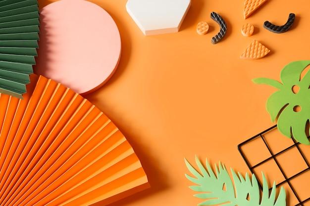 Moderne compositie van geometrische vormen, zeshoeken en cirkels, papieren waaiers, monsterabladeren en zwart raster op een oranje achtergrond plat gelegd