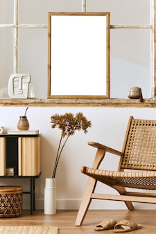 Moderne compositie van woonkamer interieur met design fauteuil, houten plank, oud raam, gedroogde bloemen in vaas, bruin mock up posterframe, decoratie en elegante persoonlijke accessoires. sjabloon.