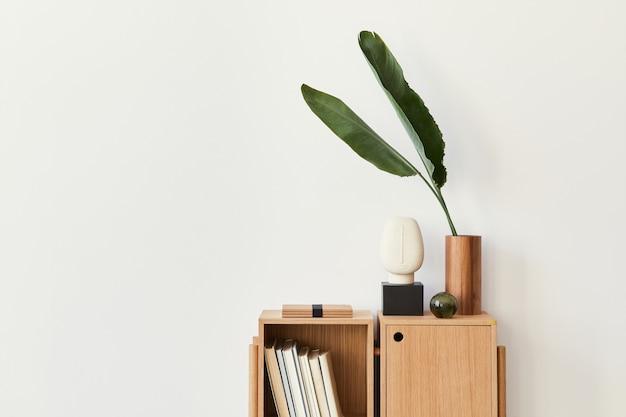Moderne compositie van woonkamerinterieur met design houten boekenkast, tropisch blad in vaas, boek, decoratie, glazige bal en kopieerruimte op de witte muur..