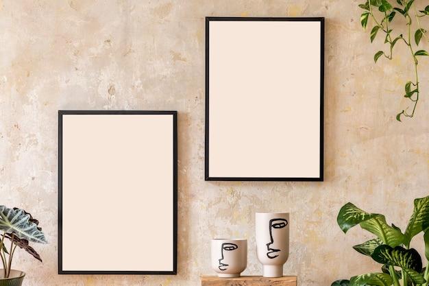 Moderne compositie van woonkamerinterieur met twee zwarte mock-up posterframes, houten kubus, planten en potten. stijlvolle woondecoratie. grungemuur. wabi sabi. sjabloon.