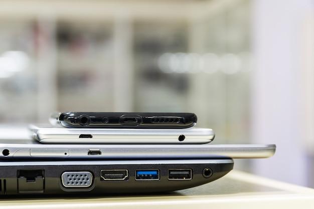 Moderne computergadgets liggen in de winkel. smartphones en tablets zijn op de laptop. zijaanzicht, close-up, selectieve aandacht