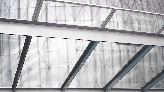 Moderne constructie van metaal en glas in zakenwijk tegen blauwe lucht