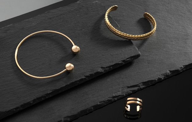 Moderne design gouden handboeien en ring op donkere stenen platen op zwarte achtergrond