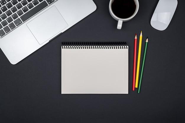 Moderne designer bureau tafel met lege notebook pagina, laptopcomputer en kopje koffie