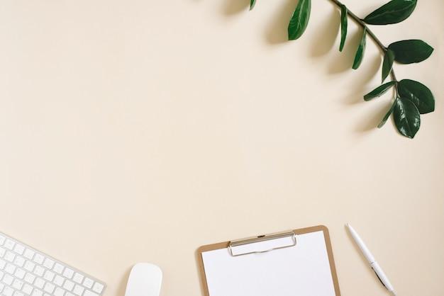 Moderne desktop van een freelancer of blogger met een toetsenbord, muis, pen en notitieblok met een blanco vel papier op een lichtbeige achtergrond met kopieerruimte. plat leggen