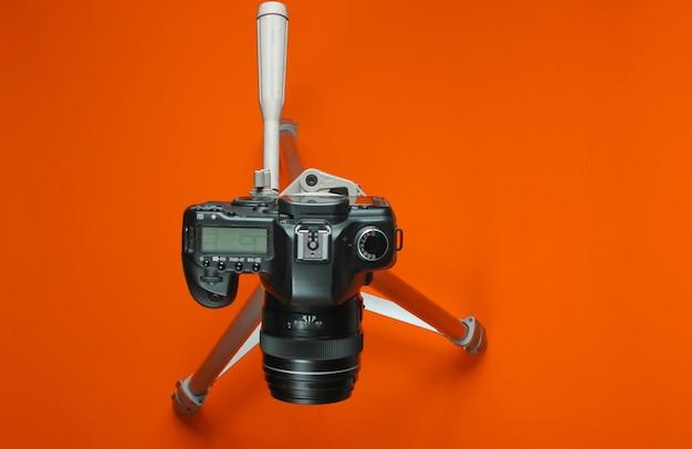 Moderne digitale camera met statief op oranje achtergrond. bovenaanzicht