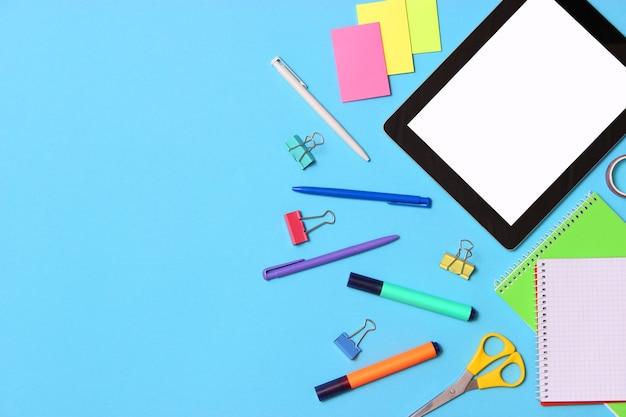 Moderne digitale tablet en schoolbenodigdheden op een gekleurd bovenaanzicht als achtergrond