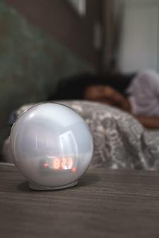 Moderne digitale wekker die de tijd aftelt tot ontwaken op het nachtkastje