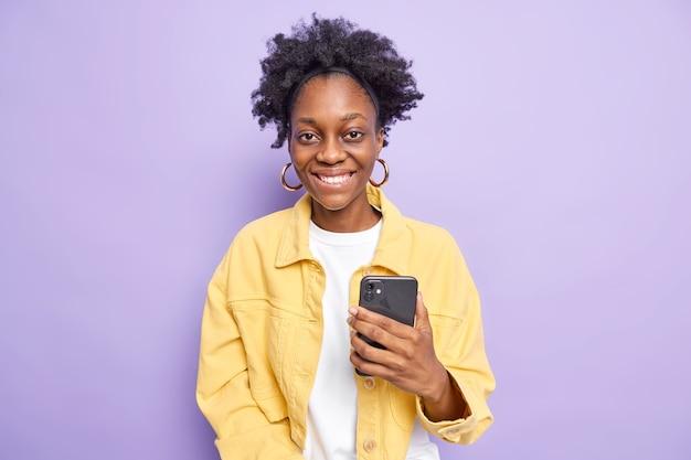 Moderne donkere afro-amerikaanse vrouw met natuurlijk krullend haar chats op telefoon maakt gebruik van mobiele telefoon houdt smartphone aangenaam glimlacht