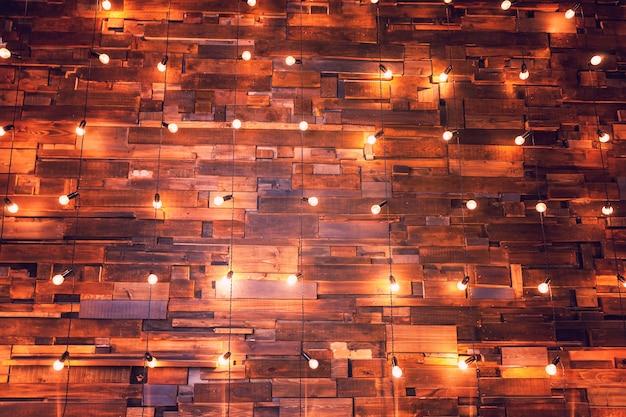 Moderne donkere klassieke stijl interieur appartement met retro lampen hangende gloeilampen achtergrond. houten planken met lampen. ingerichte binnenkamer met gouden lichten. kopieer ruimte mockup poster.