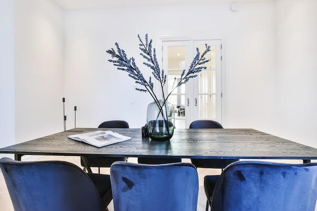 Moderne eettafel met set blauw fluwelen stoelen en vaas met bloemen bovenop in eetkamer van klassiek appartement