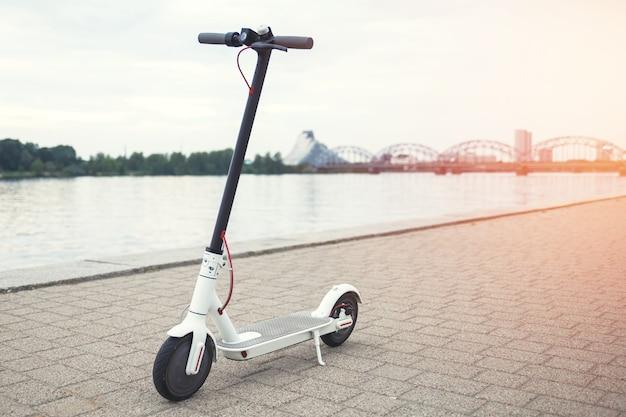 Moderne elektrische scooter aan de rivieroever van de stad
