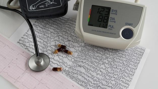 Moderne elektrische tonometer en een stethoscoop op een cardiogram-grafiek. huishoudelijke bloeddrukmeter