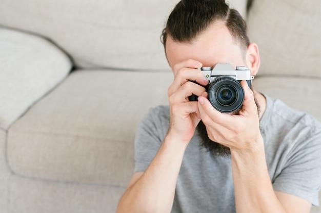 Moderne elektronicatechnologie voor creatieve vrijetijdsbesteding. man fotocamera in handen houden en door de lens kijken.